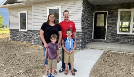 Nicole and Derek Agler and sons in front of the 2020 Tri Star house.