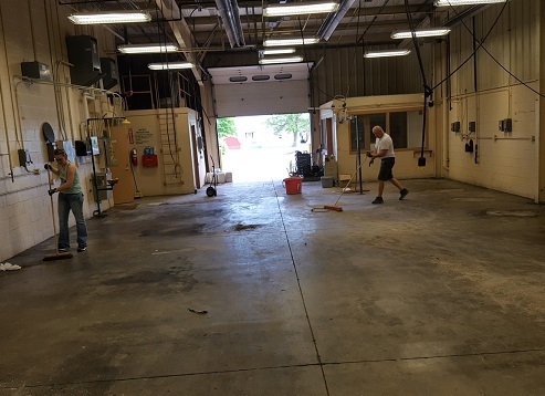 Med Prep Teacher and Precision Machining Teacher Rob Menker sweep the floor at the Dennings Bldg.: Featured Image 1
